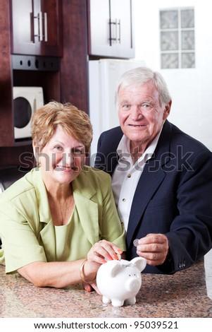 retirement savings concept: senior couple putting coins in piggybank - stock photo