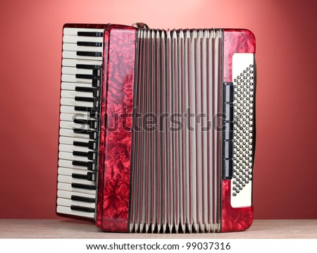 Retro accordion on wooden table on red background - stock photo
