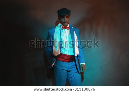 Retro african american man in blue suit wearing blue cap. Leaning against gray wall. - stock photo
