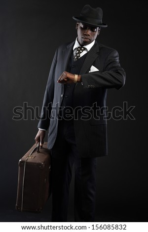 Retro african american traveller wearing striped suit and tie and black hat. Holding suitcase and looking on his watch. Studio shot. - stock photo
