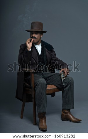 Retro afro america western cowboy man with mustache. Sitting in wooden chair holding a gun. Smoking a cigar. Wearing brown hat. Cool tough guy. - stock photo