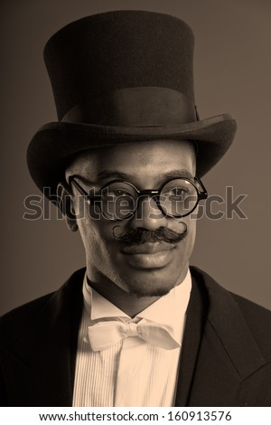 Retro afro american dickens scrooge man with mustache. Wearing black hat and glasses. Close-up portrait.