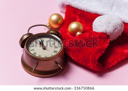 Retro alarm clock and Santa Claus hat on pink background