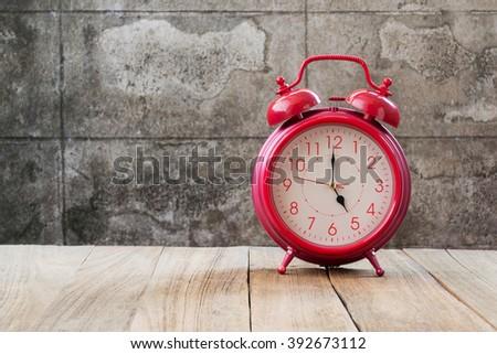 retro alarm clock (5 o'clock) on wood table  - stock photo