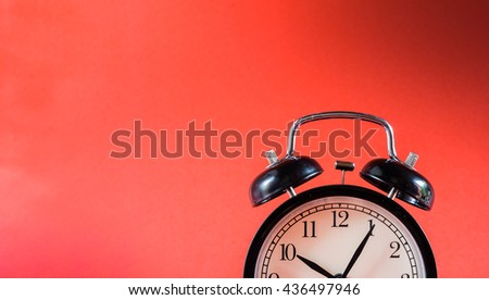 Retro alarm clock on red background,