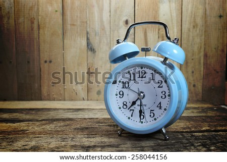 Retro alarm clock on the old wood background - stock photo