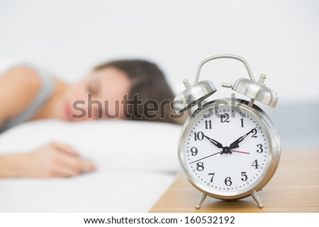 Retro alarm clock standing on bedside table with sleeping woman in background