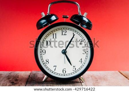 Retro alarm clock with  5 o'clock five minutes. Vintage style colour. clock concept. - stock photo