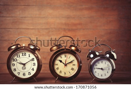 Retro alarms clock on a table. Photo in retro color image style - stock photo