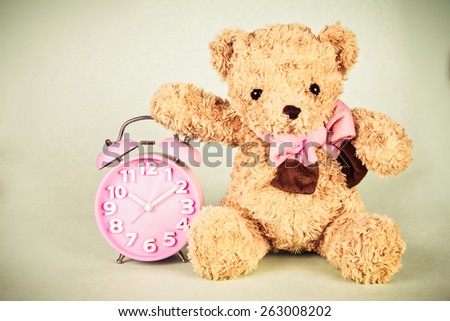 retro and vintage style of the Old fashioned alarm clock and cute brown bear doll - stock photo