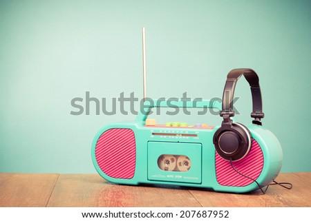 Retro aquamarine radio cassette recorder and headphones on table - stock photo