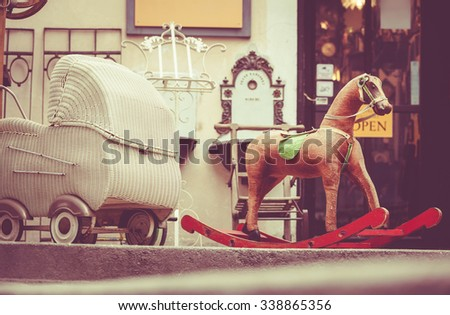 Retro baby carriage and toy rocking-horse antique sale - stock photo