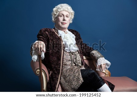 Retro baroque man with white wig holding a walking stick sitting on antique couch. Studio shot against blue. - stock photo