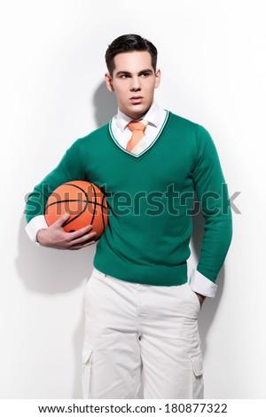 Retro basketball fashion man wearing a green sweater orange tie and white shorts. Studio shot against white wall. - stock photo