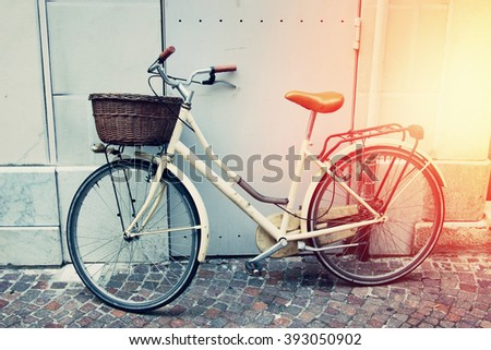 Retro bicycle with the basket on the street. Filtered image. - stock photo
