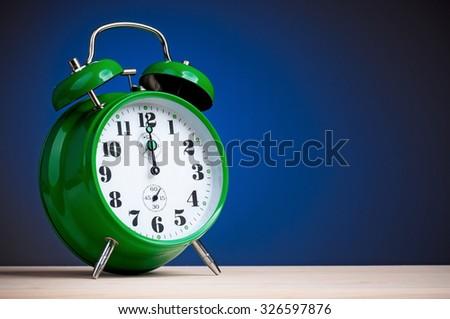 Retro big green alarm clock on blue background - stock photo
