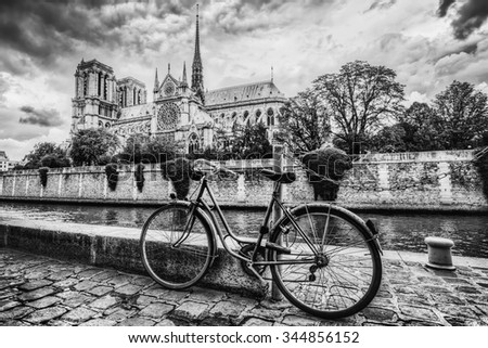 Retro bike next to Notre Dame Cathedral in Paris, France and the Seine river. Black and white vintage - stock photo