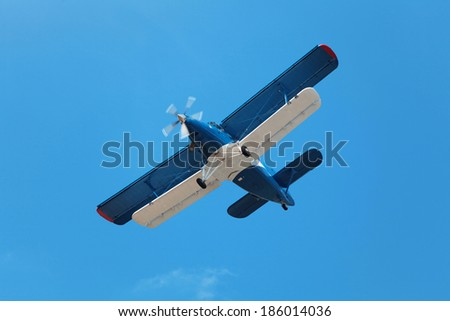 Retro-biplane aircraft, against the blue sky
