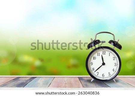 Retro ,black classical alarm clock on blurred spring background. - stock photo