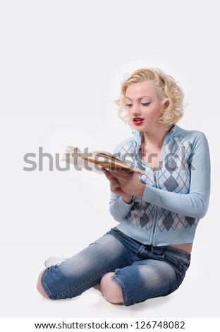 Retro blond woman sitting on the floor and reading the book