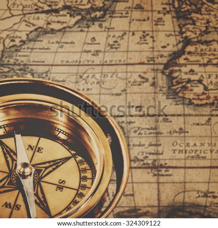 Retro brass compass over antique paper map, adventure backgrounds - stock photo
