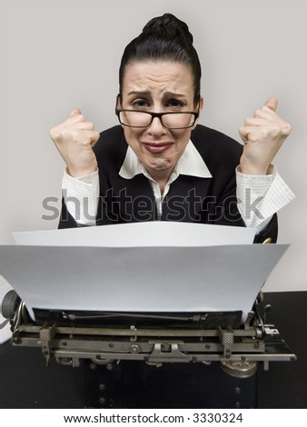 Retro business woman at vintage typewriter looking frustrated - stock photo
