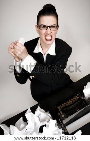 Retro business woman with vintage typewriter crumpling a paper - stock photo