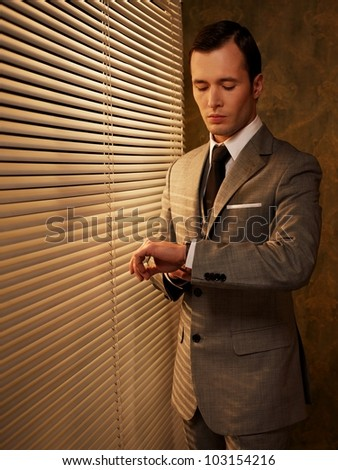 Retro businessman looking at his watch - stock photo