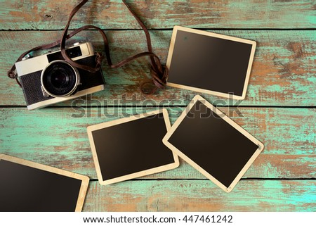 Retro camera and empty old instant paper photo album on wood table - blank photo frame vintage style - stock photo
