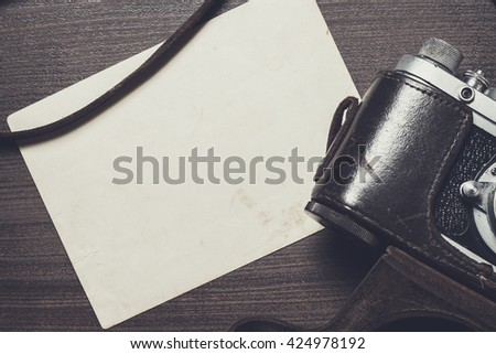 retro camera and old photos on brown wooden table - stock photo