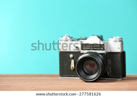 Retro camera on table on green background - stock photo