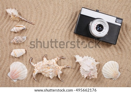 Retro Camera with shells on the sand