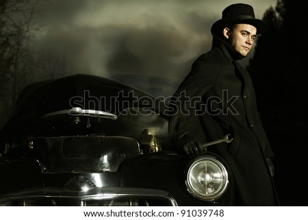 retro car and the man on the road - stock photo