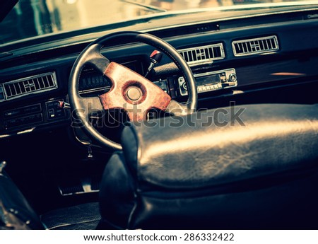 Retro car in vintage toned film effect. Interior of an old automobile with a steering wheel and dashboard. Retro design of the seventies - american car style, inside of car salon. - stock photo