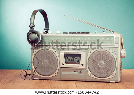 Retro cassette ghetto blaster and headphones in front mint green background - stock photo