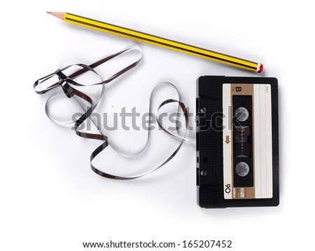 retro cassette with loose tape and a pencil to rewind over a white background - stock photo