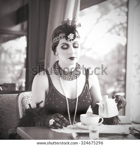 Retro Charleston Woman Sitting with in a Restaurant Holding a Cup of Tea. Black and White Portrait of The Beautiful Retro Woman Drinking Tea in Cafe in Black Lace and Accessories in Style 1920 - 1930  - stock photo