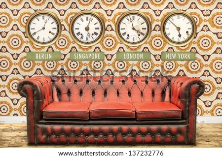 Retro chesterfield sofa with world time clocks on a wall with vintage wallpaper - stock photo