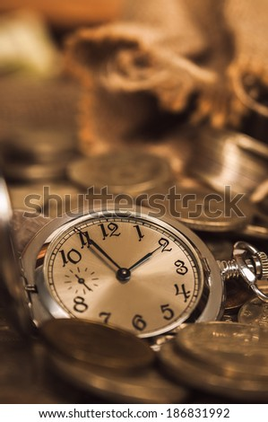 Retro clock lying in heap of coins