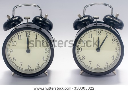 Retro clock on wooden texture front dark blue wall background. Vintage effect. 5 minutes - stock photo