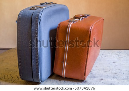 Retro closed blue and orange travel suitcases standing on the wooden surface, orange background