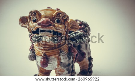 Retro color ceramic ancient lion mythical creature statue. Symbol of luck and prosperity for chinese and asian sculpture. Slightly defocused and close-up shot. Copy space. - stock photo