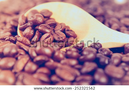 retro color tone of roasted coffee beans in wooden spoon placed on coffee beans as background , selective focus - stock photo