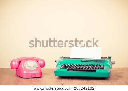 Retro color typewriter and rotary telephone on table - stock photo