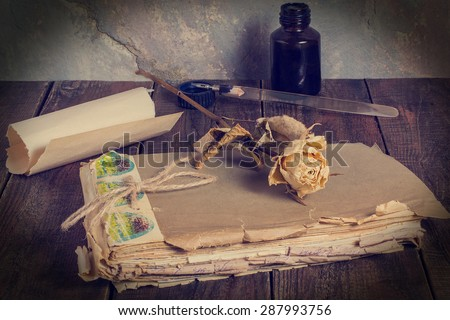 Retro composition: old worn notebook, ink bottle, a pen and a piece of dried rose yellowed paper on a wooden table at an old wall. Tinted photos - stock photo