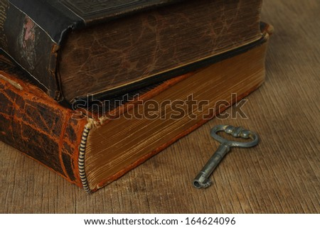 Retro composition with books and key on wooden background - stock photo