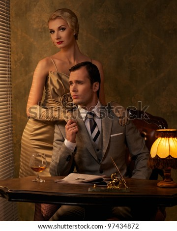 Retro couple sitting behind table. - stock photo