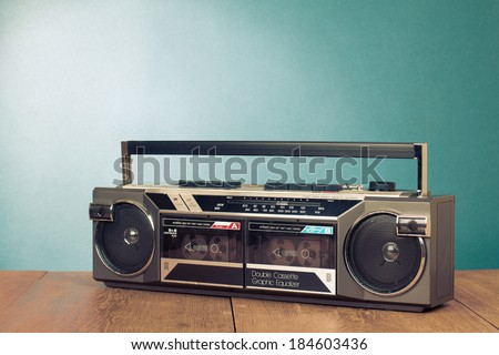 Retro double cassette tape recorder on table front mint green background - stock photo