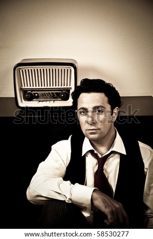 Retro - dressed up man sitting in front of old radio looking at camera