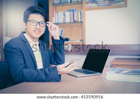 Retro effect and toned image of a man with computer laptop and Smart phone with blank screen computer for customize. Concept finance technology of business man with computer.